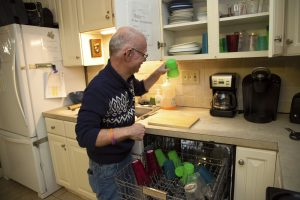 group home resident unloading dishwasher